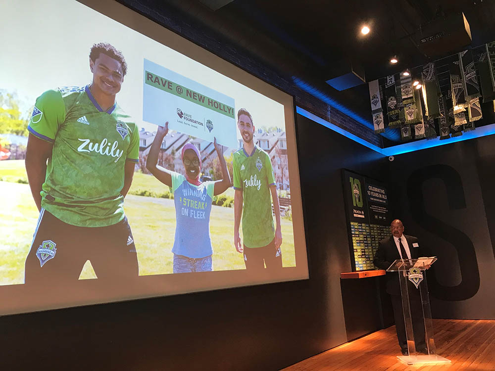 Man at podium surrounded by Sounder soccer paraphernalia