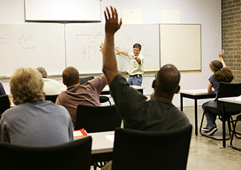 man raises hand in adult education classroom