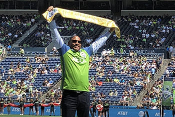SHA Executive Andrew Lofton holds up Golden Scarf presented by Seattle Sounders FC