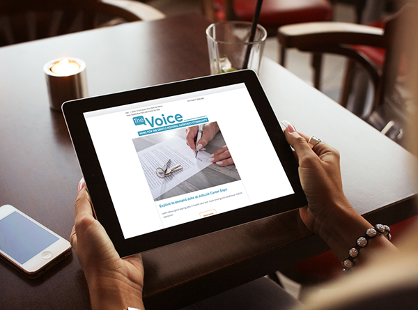 Woman's hands holding iPad with The Voice newsletter on it