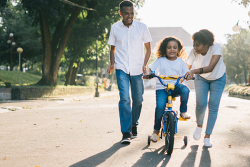 Girl learning to ride bike with two people assisting