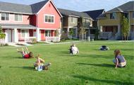 Children playing on a field in front of housing