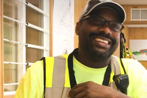 A man smiling and wearing construction work clothes