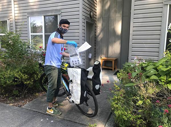 Young man delivering masks by bicycle